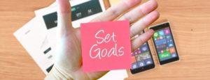 Eine Hand hält ein Post-It Note mit der Aufschrift Set Goals
